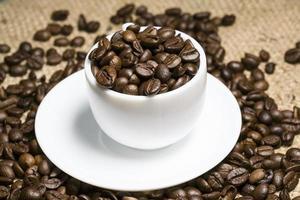 café em grão, copo branco foto