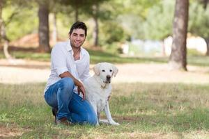 homem latino bonito com velho cão labrador sênior foto