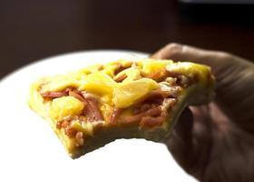 delicioso com pizza havaiana na mão
