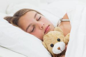 menina alegre dormindo com seu ursinho de pelúcia foto