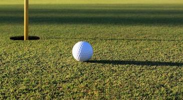 bola de golfe perto do copo foto