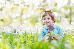 criança usando orelhas de coelho de Páscoa e comer chocolate foto