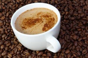 xícara de café em um fundo de grãos de café foto