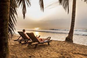casal nas espreguiçadeiras na praia tropical foto