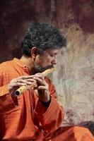 tocando flauta de homem do Sul da Ásia foto