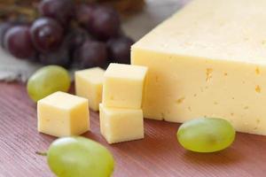 queijo e uvas em cima da mesa foto
