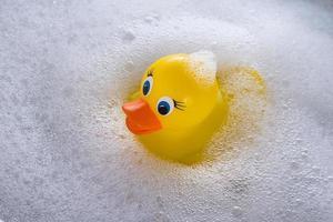 pato de borracha amarelo flutuando na espuma de sabão foto