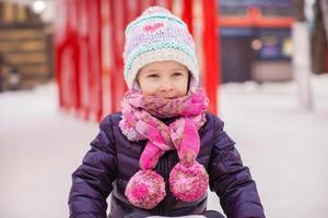 adorável menina feliz patinando na pista de gelo foto