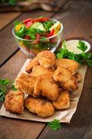nuggets de frango e molho em um fundo de madeira foto