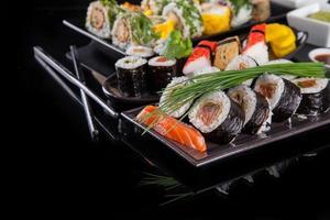 pedaços de sushi delicioso em fundo preto foto