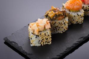 rolos de sushi em um prato de pedra