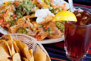nachos, batatas fritas e chá gelado foto