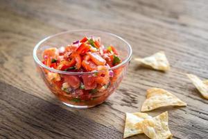 tigela de salsa com batatas fritas de pacote foto