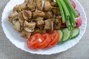 mini espetos de frango e um prato de legumes