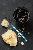 batatas fritas e copo de coca-cola em cima da mesa foto