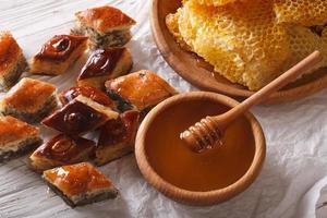 doces orientais: baklava com papoula e nozes e um favo de mel. foto