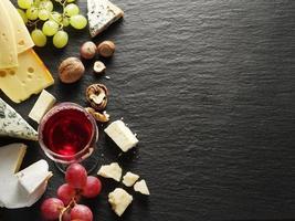 tipos de queijos com copo de vinho e frutas.
