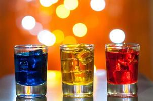 três copos com licor de frutas no bar em um foto