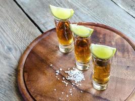 copos de tequila na placa de madeira