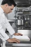chef masculino lendo livro de receitas na cozinha foto