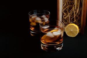 Óculos wiskey em fundo escuro. foto