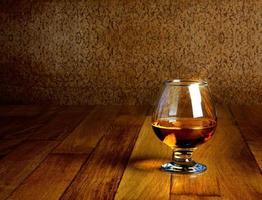 um copo de conhaque na bancada de madeira antiga
