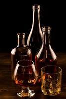 copo de uísque com gelo e garrafa na mesa de madeira. foto