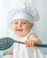 bebê no chef capuz com utensílios de cozinha foto