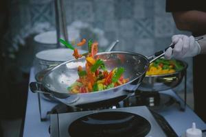 cozinhar legumes na panela wok foto