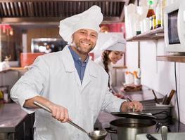 chef e seu ajudante na cozinha de bistrô foto