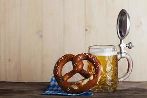 cerveja da Baviera e um pretzel na madeira foto