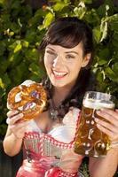 feliz mulher da Baviera com vestidos casuais, cerveja e pretzel foto