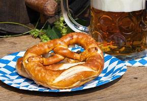 cerveja e pretzel em um prato de papel foto