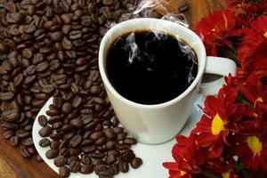 xícara de café e feijão em um fundo de madeira. foto