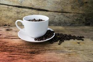 xícara cheia de grãos de café na madeira foto