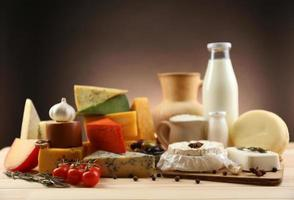 saborosos produtos lácteos na mesa de madeira, em fundo escuro foto