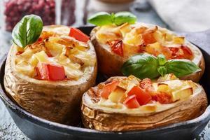 batatas recheadas com queijo e tomate em uma panela foto