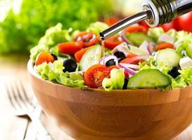 óleo derramando na tigela de salada de legumes foto
