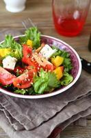 salada com tomate, queijo e verduras em uma tigela foto