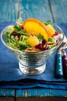 salada saudável mistura com laranja e nozes em vidro foto