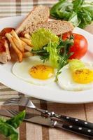 ovos fritos com linguiça e batatas fritas foto