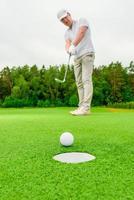 homem de imagem vertical jogando golfe em um campo verde foto