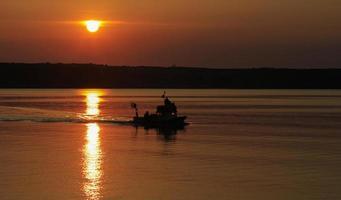 barco de peixe e pôr do sol foto