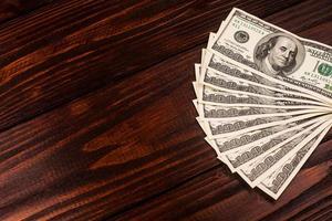 dólares na mesa de madeira foto