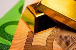 notas de euro e dois lingotes de ouro foto