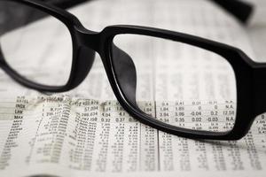 closeup óculos no jornal financeiro foto