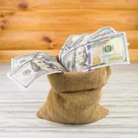 dólares em fundo madeira foto