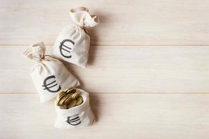 sacos de dinheiro com moedas de euro na luz de fundo de madeira foto