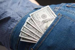 maço de notas de dólar no bolso da mulher jeans foto