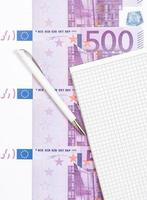 várias notas de euro ao lado do bloco de notas foto